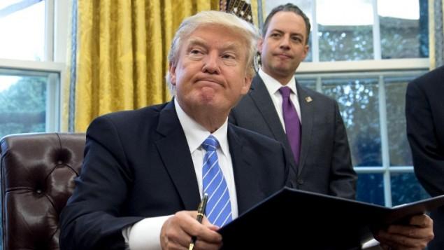 الرئيس الأمريكي دونالد ترامب يوقع على أمر تنفيذي وإلى جانبه يقف كبير الموظفين في البيت الأبيض رين بريبوس في المكتب البيضاوي في البيت الأبيض، العاصمة الأمريكية واشنطن، 23 يناير، 2016. (AFP PHOTO / SAUL LOEB)
