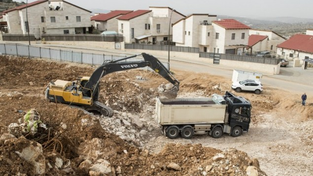 عمال فلسطينيون في موقع بناء لمشورع بناء وحدات سكنية جديدة في مستوطنة أريئيل بالقرب من مدينة نابلس في الضفة الغربية، 25 يناير، 2017. (AFP Photo/Jack Guez)