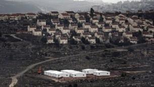 منازل جاهزة جديدة قيد البناء في الضفة الغربية بين بؤرة عامونا الإستيطانية ومستوطنة عوفرا الإسرائيلية (في الخلفية)، شمال رام الله، 31 يناير، 2017. (AFP PHOTO / THOMAS COEX)
