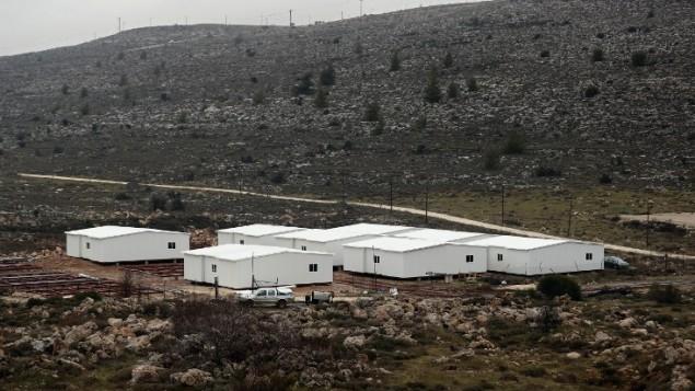 منازل جاهزة قيد الإنشاء في الضفة الغربية بين بؤرة عامونا الإستيطانية (في الخلفية) ومستوطنة عوفرا الإسرائيلية، شمال رام الله، 31 يناير، 2017. ( AFP/ THOMAS COEX)