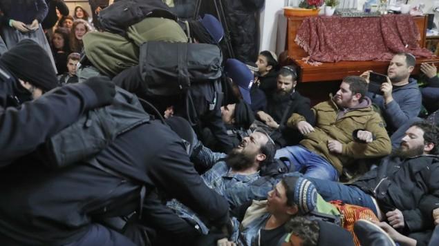 مستوطنون اسرائيليون يشتبكون مع قوات الامن خلال اخلاء بؤرة عامونا الاستيطانية في الضفة الغربية، 1 فبراير 2017 (AFP/Jack GUEZ)