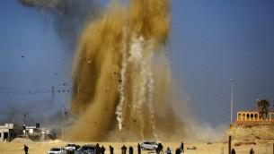 الفلسطينيون يبحثون عن مخبأ مع تصاعد الرمال والدخان في أعقاب غارة جوية إسرائيلية ضد موقع تابع لحركة 'حماس' شمال قطاع غزة، 6 فبراير، 2017. (Mohammed Abed/AFP)