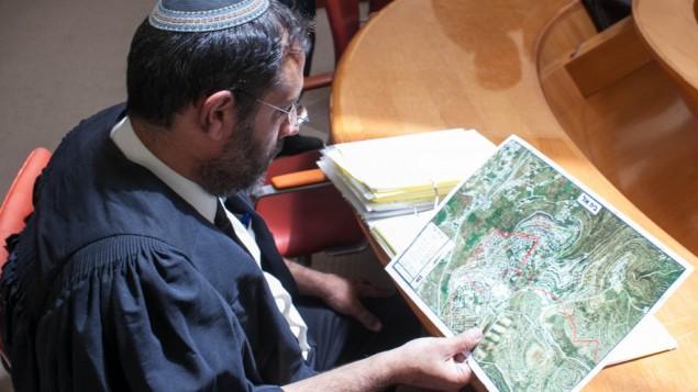 محام يدقق النظر في خريطة لمستوطنة بيت إيل قبل جلسة في المحكمة العليا في عام 2012. (Noam Moskowitz/Flash90)