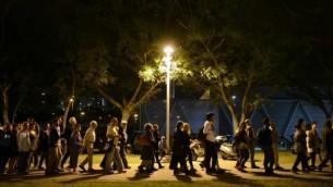 فلسطينيون وإسرائيليون يشاركون في مراسم مشتركة لعائلات ضحايا إسرائيليين وفلسطينيين في يوم ذكرى ضحايا الحروب الإسرائيلية، التي نظمتها منظمتا 'مقاتلون من أجل السلام' و 'منتدى العائلات الثكلى الفلسطيني-إسرائيلي من أجل السلام' في تل أبيب، 21 أبريل، 2015. (Tomer Neuberg/Flash90)