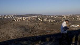 رجل يصلي في بؤرة عامونا الإستيطانية غير القانونية، ومشهد لمستوطنات في الضفة الغربية في الخلفية، 2 فبراير، 2017. (Yonatan Sindel/Flash90)