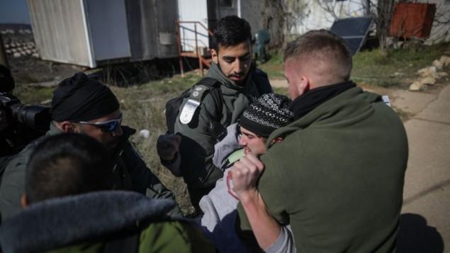 عناصر الشرطة الإسرائيلية يخرجون بالقوة شاب من كنيس بؤرة عامونا الاستيطانية في اليوم الثاني لعملية اخلاء البؤرة، 2 فبراير 2017 (Yonatan Sindel/Flash90)