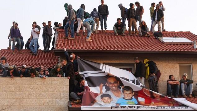 محتجون يجلسون على سطح أحد المنازل خلال عملية إخلاء تسع منازل في مستوطنة عوفرا اليهودية في الضفة الغربية، 28 فبراير، 2017. (Hadas Parush/Flash90)