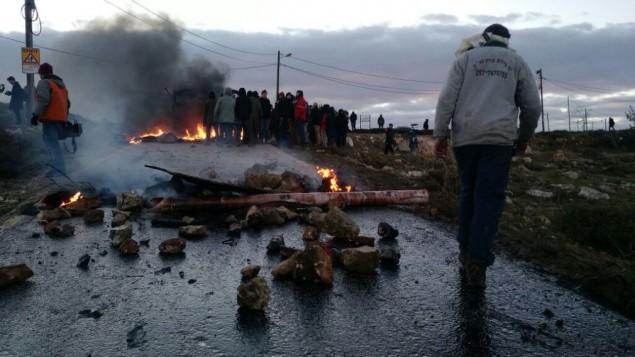نشطاء من المستوطنين يحرقون الإطارات ومواد أخرى عند مدخل بؤرة عامونا الإستيطانية وسط الضفة الغربية في الوقت الذي تستعد فيه قوى الأمن الإسرائيلية لإخلاء المستوطنة غير الشرعية، 1 فبراير، 2017. (Judah Ari Gross)