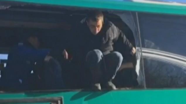 محتجون تم إخلاؤهم من الكنيس في عامونا يحطمون زجاج حافلة ويلوذون بالفرار بعد أن وضعتهم الشرطة داخل المركبة، خلال إخلاء البؤرة الإستيطانية، 2 فبراير، 2017. (لقطة شاشة: القناة 10)