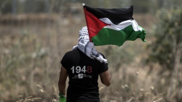 شاب فلسطيني يحمل العلم الفلسطيني في الوقت الذي يقوم فيه الجيش الإسرائيلي بالبحث عن أنفاق تهريب على الحدود الشرقية لمدينة غزة، 15 مايو، 2016، في الذكرى ال68 ل'النكبة'، (AFP/Mahmud Hams)