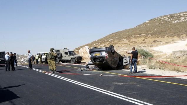 الشرطة الإسرائيلية تجمع الأدلة من موقع الهجوم الذي قُتل فيه الحاخام ميكي مارك وأصيب ثلاثة من أفراد عائلته عندما قام منفذ هجوم فلسطيني بفتح النار على مركبته، 1 يوليو، 2016، جنوبي الخليل. (AFP/Hazem Bader)