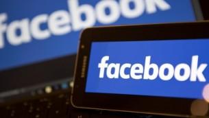 صورة الأرشيف هذه تم إلتقاطها في 21 نوفمبر، 2016، وتظهر شعار فيسبوك على هاتف ذكي (من اليسار) وجهاز كمبيوتر محمول، في وسط لندن. (AFP)