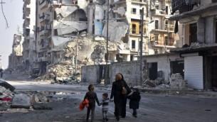 سوريون يسيرون بين المباني المدمرة في حي طريق الباب في مدينة حلب، 18 يناير، 2017، بعد شهر من نجاح القوات الحكومية بإستعادة السيطرة على المدينة التي تقع شمال البلاد من المتمردين. (AFP Photo/George Ourfalian)