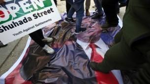 متظاهرون فلسطينيون يقفون على صورة للرئيس الأمريكي دونالد ترامب خلال تظاهرة ضد دعمه لإسرائيل ومطالبة الجيش الإسرائيلي بإعادة فتح شارع الشهداء القريب من جيب استيطاني يهودي في قلب مدينة الخليل، 24 فبراير، 2017. (AFP/Hazem Bader)