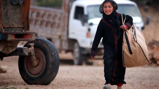 طفلة نازحة سورية، فرت من بلدتها بسبب المعارك بين قوات النظام وتنظيم الدولة الإسلامية، تحمل حقيبة في قرية خاروفية، على بعد 18 كيلومترا جنوب منبج،  4 مارس، 2017. (AFP PHOTO / DELIL SOULEIMAN)