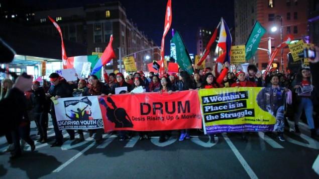 مشاركون في مسيرة لحركة 'الإضراب العالمي للنساء' في 8 مارس، 2017 في مدينة نيويورك.  حشود من المتطاهرين، معظمهم من النساء واللواتي ارتدى الكثير منهن الأحمر، ساروا في نيويورك وواشنطن الأربعاء للإحتجاج على سياسات الرئيس الأمريكي دونالد ترامب تجاه النساء في يوم المرأة العالمي. (AFP PHOTO / KENA BETANCUR)
