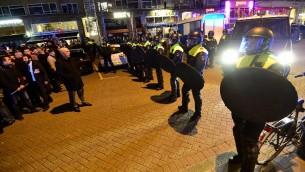 عناصر شرطة تواجه متظاهرين احتشدوا أمام القنصلية التركية في روتردام في 11 مارس، 2017. (AFP PHOTO / EMMANUEL DUNAND)