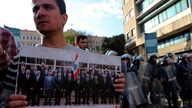 متظاهر يحمل لافتة عليها صورة وزراء لبنانيين ومكتوب عليها 'لصوص من لبنان'، خلال مظاهرة ضد قرار رفع الضرائب في بيروت، 19 مارس 2017 (STR / AFP)