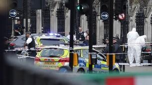 عناصر شرطة مسلحة يقومون في الحراسة بينما يقوم عناصر البحث الجنائي بالعمل في محيط مركبة رمادية اللون اصطدمت  بحواجز مبنى البرلمان البريطاني في وسط لندن، 22 مارس، 2017. (AFP PHOTO / Daniel LEAL-OLIVAS)