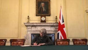 رئيسة وزراء بريطانيا تيريزا ماي، تجلس تحت لوحة لرئيس وزراء بريطانيا الأول روبرت والبول، خلال توقيعها على الرسالة الرسمية لرئيس المجلس الأوروبي دونالد توسك، لتفعيل المادة 50 والإعلان عن نية بريطانيا الخروج من الإتحاد الأوروبي، في مقر الحكومة في 10 داونينغ ستريت، 28 مارس، 2017. (AFP PHOTO / POOL / CHRISTOPHER FURLONG)