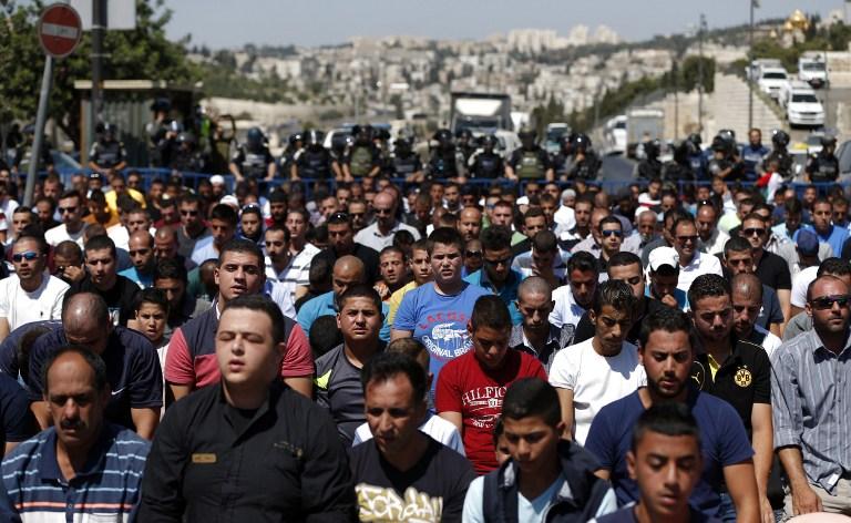 قوى الأمن الإسرائيلية تقوم بالحراسة في الوقت الذي يشارك فيه مصلون مسلمون في صلاة يوم الجمعة في حي راس العامود في القدس الشرقية، 18 سبتمبر، 2015. (AFP PHOTO/AHMAD GHARABLI)