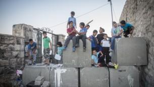 اطفال فلسطينيون فوق حاجز اسمنتي وضعه الجيش الإسرائيلي في حي راس العامود في القدس الشرقية، 21 اكتوبر 2015 (Hadas Parush/Flash90)