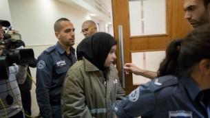 فتاة فلسطينية تبلغ من العمر 16 عاما تصل إلى قاعة المحكمة المركزية في القدس في 11 ديسمبر، 2015، حيث تم توجيه تهمتين بالشروع بالقتل في هجوم طعن وقع في 23 نوفمبر في العاصمة. (Yonatan Sindel/Flash90)