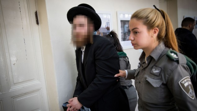 رجل يهودي تقوده الشرطة داخل محكمة الصلح، بعد اعتقال الشرطة 22 يهوديا متشددا بتهمة الاعتداء جنسيا على نساء، شبان واطفال، 27 مارس 2017 (Yonatan Sindel/Flash90)