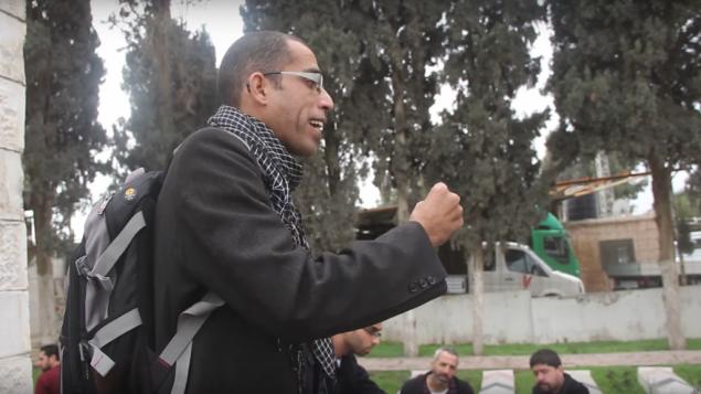 باسل الأعرج، الذي قُتل في تبادل لإطلاق النار مع القوات الإسرائيلية في 6 مارس، 2017، يتحدث أمام مجموعة من الأشخاص في مقبرة في قلنديا، شمال الضفة الغربية، 19 ديسمبر، 2014. (Screen capture: YouTube)