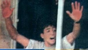 عبد العزيز صالح يلوح بيديه الملطختين بالدماء بعد الإعتداء بالضرب الوحشي على جنديين إسرائيليين في رام الله في عام 2000. (screen capture, YouTube)