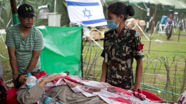 سيدة نيبالية مصابة تصل على حمالة لتلقي العلاج في مستشفى ميداني إسرائيل في كاتماندو، 1 مايو، 2015، في أعقاب زلزال مدمر بقوة 7.8 على سلم ريختر ضرب الدولة التي تقع في جبال الهملايا، 25 أبريل، 2015. (AFP PHOTO / MENAHEM KAHANA)