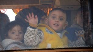 طفل سوري يلوح من شباك حافلة خلال اخلاء بلدة في محافظة حمص السورية، 19 مارس 2017 (AFP PHOTO / Nazeer al-Khatib)