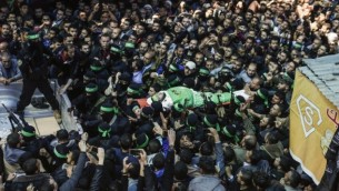 عناصر من كتائب عز الدين القسام، الجناح العسكري لحركة حماس، يشيعون جثمان مازن الفقهاء خلال جنازته في مدينة غزة، 25 مارس، 2017. (AFP PHOTO / MAHMUD HAMS)