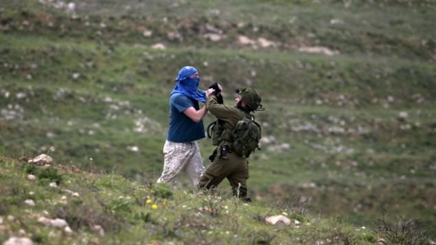 جندي إسرائيلي يشتبك مع مستوطن إسرائيلي ملثم خلال محاولة إبعاده عن منطقة يجري فيها فلسطينيون تظاهرة لإحياء ذكرى 'يوم الأرض'، في قرية مادما، جنوب مدينة نابلس في الضفة الغربية، 30 مارس، 2017. (AFP/JAAFAR ASHTIYEH)