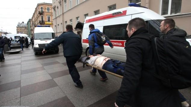 رجال يحملون شخص مصاب خارج محطة مترو في سان بطسبرغ، 3 ابريل 2017 (AFP Photo /Inet Press/Alexander Tarasenkov)