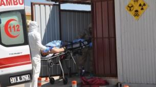 مسؤولون أتراك يرتدون ملابس مضادة للمواد الكيميائية يحملون رجلا مصابا قي 4 أبريل، 2017 في محافظة هاتاي، القريبة من الحدود السورية. (AFP/ DOGAN NEWS AGENCY)