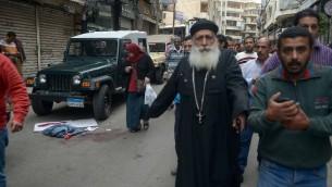 مصريون يمرون امام يقع دم في شارع قريب لكنيسة في الإسكندرية استُهدفت في انفجار خلال احتفال المصلين بأحد الشعانين، 9 أبريل، 2017. (AFP PHOTO / STRINGER)