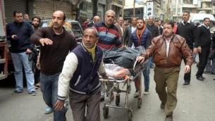 مصريون ينقلون جثمان بالقرب من كنيسة في الاسكندرية بعد تفجير استهدف المصلين خلال احد الشعانين، 9 ابريل 2017 (AFP Photo/Stringer)