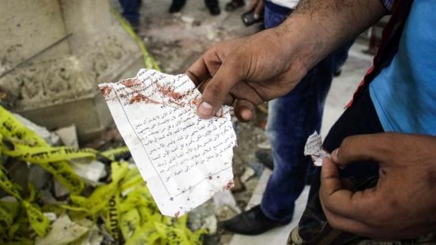رجل مصري يحمل صفحة من كتاب صلوات ملطخ بالدماء بعد تفجير في كنيسة مار جرجس القبطية في مدينة طنطا المصرية، 9 ابريل 2017 (AFP PHOTO / STRINGER)
