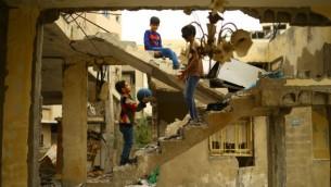 أطفال فلسطينيون يلعبون وسط أنفاض مبنى تم تدميره خلال حرب غزة 2014 في مدينة غزة، 13 أبريل، 2017. (AFP /MOHAMMED ABED)