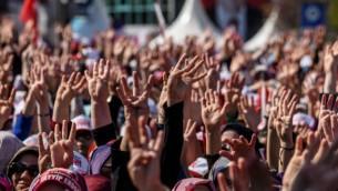 """الجماهير تهتف وترفع شعار الأصابع الأربعة الذي يرمز لشعار """"رابعة"""" خلال إلقاء الرئيس التركي لخطال في إسطنبول، 15 أبريلن 15 أبريل، 2017، خلال تجمع عشية الإستفتاء الدستوري. (Ozan Kose/AFP)"""