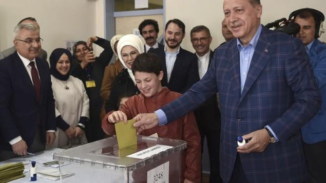 الرئيس التركي رجب طيب أردوغان (من اليمين) يدلي بصوته برفقة زوجته أمينة أردوغان (الثالثة من اليسار) وأحفادهما خلال إستفتاء على توسيع صلاحيات الرئيس في محطة إقتراع في منطقة أوسكودار في إسطنبول، 16 أبريل، 2017. (AFP PHOTO / OZAN KOSE)