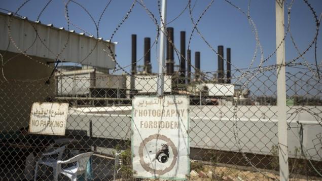 محطة الكهرباء في مدينة غزة كما تظهر في الصورة من وراء سياج في 16 أبريل، 2017. محطة الكهرباء العاملة الوحيدة في القطاع توقفت عن العمل بعد نفاذ الوقود منها، بحسب ما قاله المسؤول عن شركة الكهرباء في القطاع لوكالة فرانس برس. (AFP PHOTO / MAHMUD HAMS)
