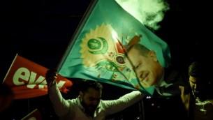 مؤيد لمعسكر 'نعم' يلوح بعلم يحمل صورة الرئيس التركي رجب طيب أردوغان خلال مسيرة بالقرب من مقر حزب 'العدالة والتنمية' المحافظ في 16 أبريل، 2017 في إسطنبول. (AFP Photo/Ozan Kose)