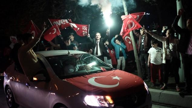 مؤيدون الرئيس التركي رجب طيب أردوغان يلوحون بالأعلام التركية خلال مسيرة بالقرب من مقر حزب 'العدالة والتنمية' المحافظ في 16 أبريل، 2017، في إسطنبول. (AFP Photo/Ozan Kose)