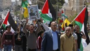 متظاهرون فلسطينيون يرفعون الأعلام الفلسطينية في مدينة بيت لحم في الضفة الغربية تضامنا مع الأسرى الفلسطينيين المضربين عن الطعام، 17 أبريل، 2017. (AFP/Ahmad Gharabli)
