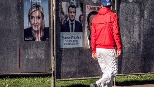 رجل يمر من  أمام جدار يحمل ملصقات إنتخابية تحمل صور مرشحة حزب اليمين المتشدد 'الجبهة الوطنية' للرئاسة الفرنسية مارين لوبن (من اليسار) ومرشح حركة 'إلى الأمام'، ايمانويل ماكرون، في هينان بومونت في شمال فرنسا، 19 أبريل، 2017. (AFP PHOTO / PHILIPPE HUGUEN)