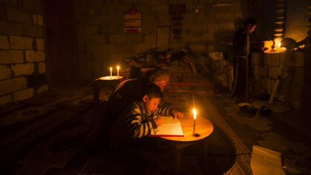امرأة فلسطينية تساعد ابنها على الدراسة على ضوء شمعة في مخيم خان يونس، شمال قطاع غزة، 19 ابريل 2017 (AFP/MAHMUD HAMS)