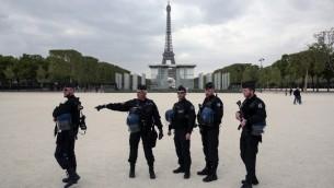 رجال شرطة فرنسيون يقفون أمام برج إيفل في باريس، 22 أبريل، 2017. ( AFP PHOTO / GEOFFROY VAN DER HASSELT)