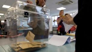ناخبة تدخل ظرفا في صندوق إقتراع في اليوم الذي يتوجه فيه المواطنون الفرنسيون المقيمون في هونغ كونغ إلى صنادئق الإقتراع للإدلاء بأصواتهم في الجولة الأولى من الإنتخابات الرئاسية الفرنسية في المدرسة الدولية الفرنسية في هونغ كونغ، 23 أبريل، 2017. ( AFP PHOTO / TENGKU Bahar)